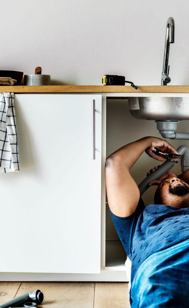 https://nolascoplumbing.com/wp-content/uploads/2021/06/plumber-man-fixing-kitchen-sink-640x1040.jpg